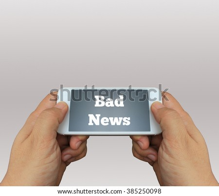a man using hand holding the smartphone with text Bad News on display - stock photo