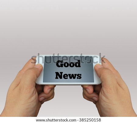 a man using hand holding the smartphone with text Good News on display - stock photo