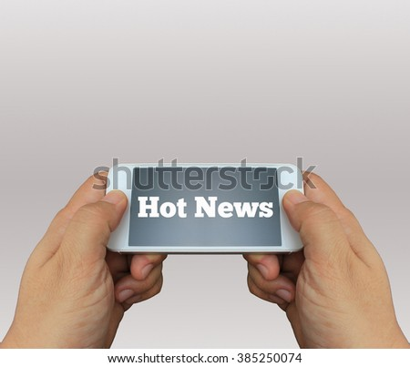 a man using hand holding the smartphone with text Hot News on display - stock photo
