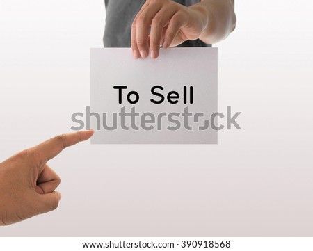 a man using hand holding the white paper with text to sell