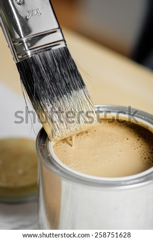 a man using paintbrush painting wooden plank - stock photo