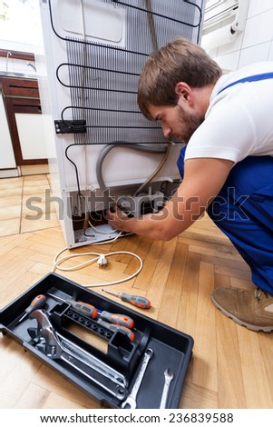 A man using tools to fix the refrigerator - stock photo