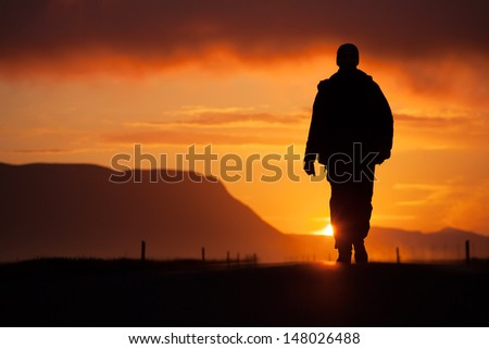 a man walking along the road, backlit at sunset, among the mountains, the clouds - stock photo