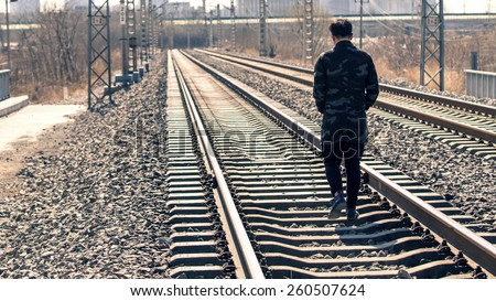 A man walking on the tracks - stock photo