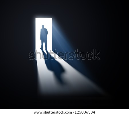 A man walking out through open doors - stock photo