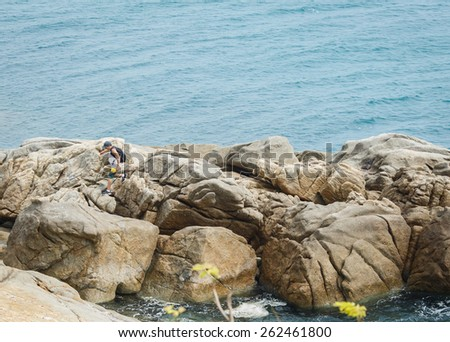 A man walks on the large rocks near the sea - stock photo
