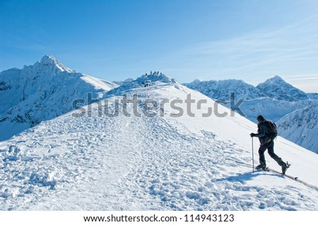 A man wandering through the mountains in winter.