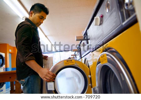 A man washing his clothes at a local laundromat. - stock photo