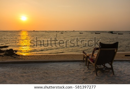 A man watching sunset in vintage beach chair