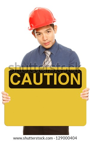A man wearing a hardhat and holding a blank caution or safety sign - stock photo