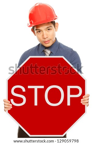 A man wearing a hardhat holding a Stop sign - stock photo