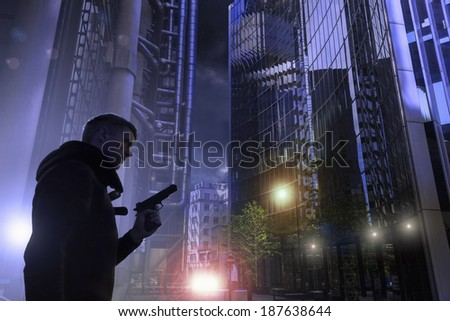 A man, wearing a hoodie, walks through a dark, modern cityscape, holding a hand gun. Surreal, sci-fi, computer game style photograph. London's financial district. - stock photo
