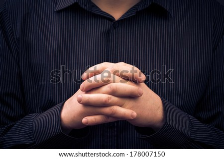 A man wearing a shirt with folded hands - stock photo
