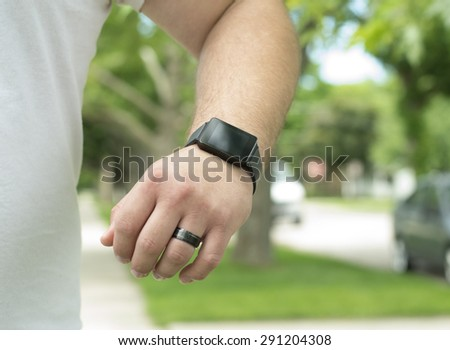 A man wearing a smart watch out for a run. - stock photo