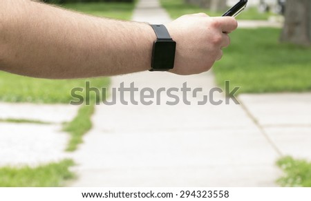 A man wearing a smartwatch and using a smartphone outside. - stock photo