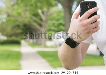 A man wearing a smartwatch and using a smartphone to take a picture outside. - stock photo