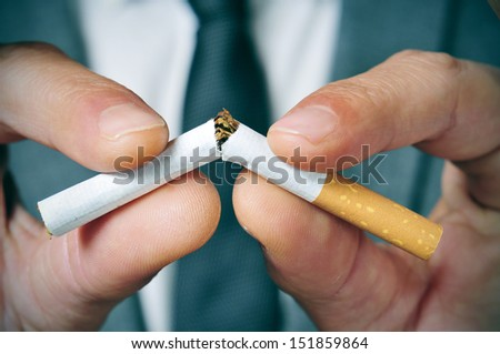 a man wearing a suit breaking a cigarette with his hands - stock photo