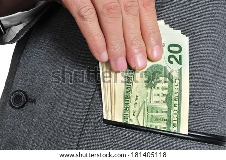 a man wearing a suit getting dollar bills in the pocket of his jacket - stock photo