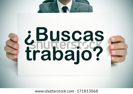 a man wearing a suit holding a signboard with the question buscas trabajo? are you looking for a job? written in spanish - stock photo