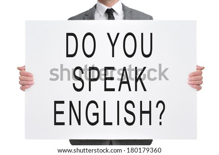 a man wearing a suit holding a signboard with the sentence do you speak english? written in it - stock photo
