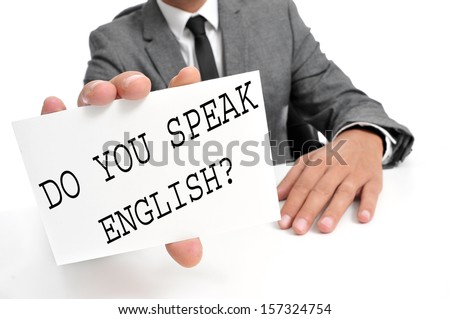 a man wearing a suit holding a signboard with the sentence do you speak english? written on it - stock photo