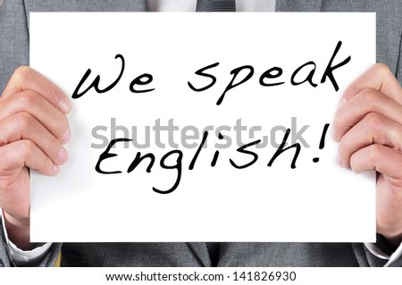 a man wearing a suit holding a signboard with the sentence we speak english written in it - stock photo