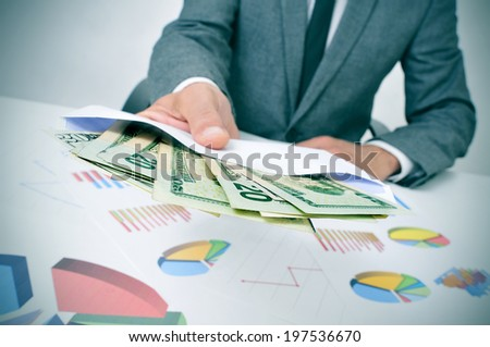 a man wearing a suit sitting in a desk giving an envelope full of dollar bills - stock photo