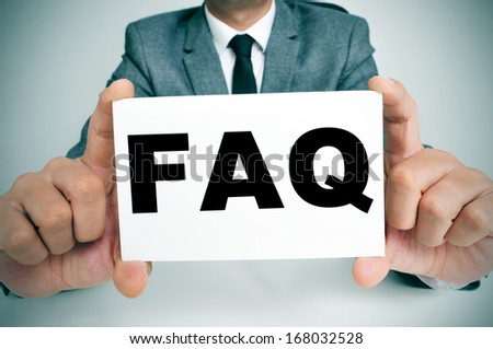 a man wearing a suit sitting in a desk holding a signboard with the word FAQ, Frequently Asked Questions, written in it - stock photo