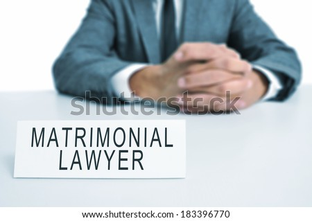 a man wearing a suit sitting in a desk with a desktop nameplate in front of him with the text matrimonial lawyer  - stock photo