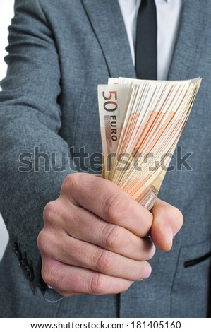 a man wearing a suit sitting with a wad of euro bills in his hand - stock photo
