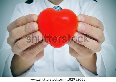 a man wearing a white coat sitting in a desk showing a red heart - stock photo