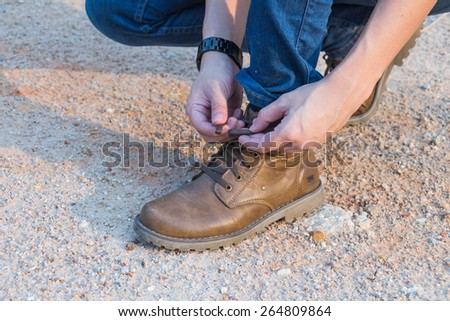 A man wearing blue jeans and brown boots lacing a shoes on the ground - stock photo