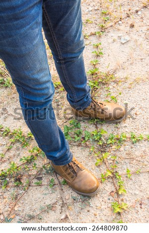 A man wearing blue jeans and brown boots standing on the ground
