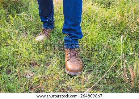 A man wearing blue jeans and brown boots walking on the grass