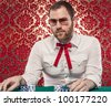 A man wearing glasses, a white shirt, and a red Texas tie sits at a blackjack table. There are stacks of blue and white chips in front of him./Confident Man Gambling Wearing Glasses, Texas Tie - stock photo