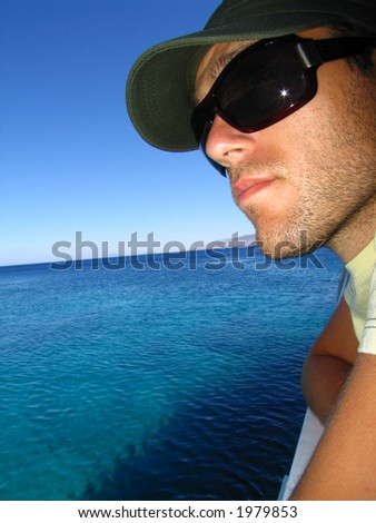 A man wearing sunglasses overlooking the Mediterranean sea.