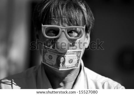 a man wears a rubber clown nose and glasses with a dollar bill taped over his mouth in protest against inflation and the rising cost of goods and services in black and white - stock photo