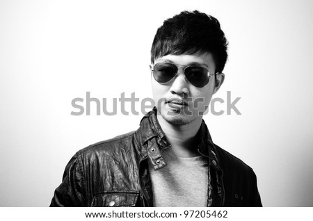 A man wears sunglasses and jacket in black and white color