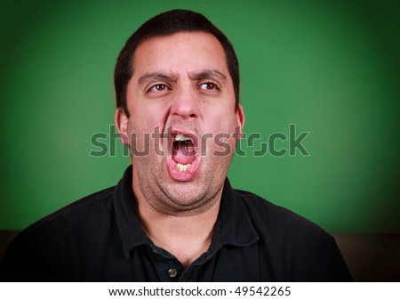 A man who appears to be yawning or belching with a green background - stock photo