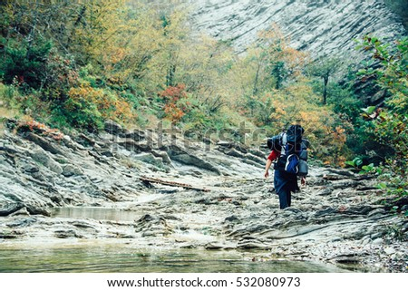 A man with a backpack going into the distance on the riverbed