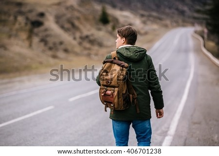 a man with a backpack walks alone upon the road - stock photo