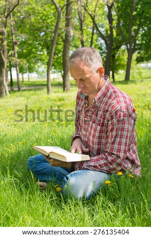 A man with a book in his hands resting in the park - stock photo