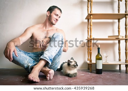 A man with a bottle of wine in his hand sitting on the floor near the cat - stock photo