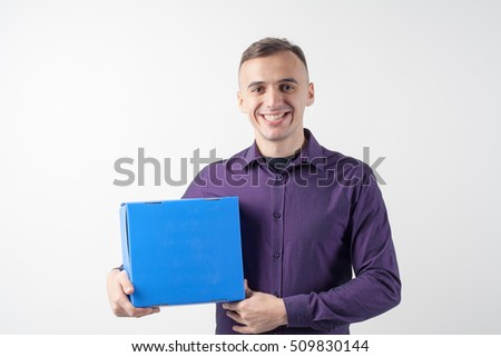A man with a box. Courier. Delivery. Blue box in a man's hands. Front view.