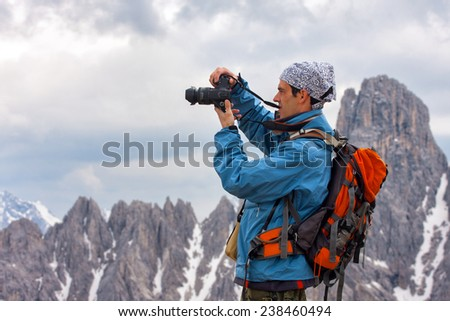 a man with a camera in mountains, Italy  - stock photo