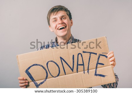 a man with a cardboard sign on the donate - stock photo