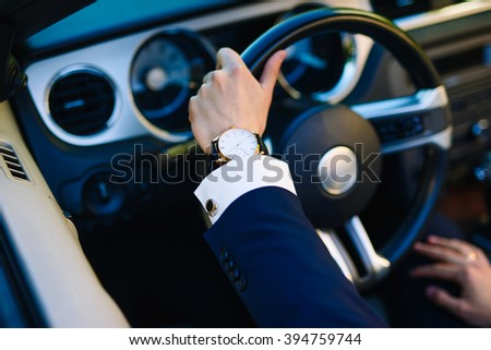 A man with a clock on the steering wheel of the car. Businessman in a suit behind the wheel