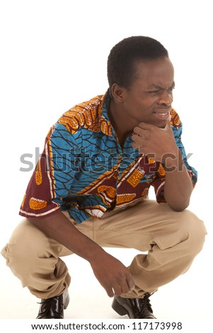A man with a confused expression on his face crouching down and thinking