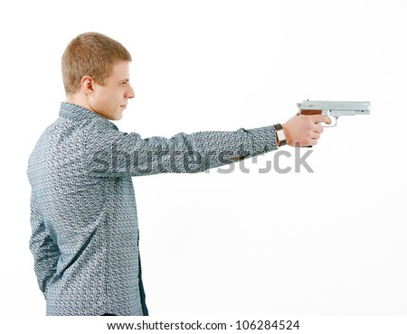 a man with a gun aiming at the distance. profile - stock photo