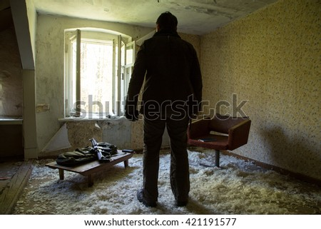 a man with a gun in abandoned house, preparing to fire, the floor of the pens